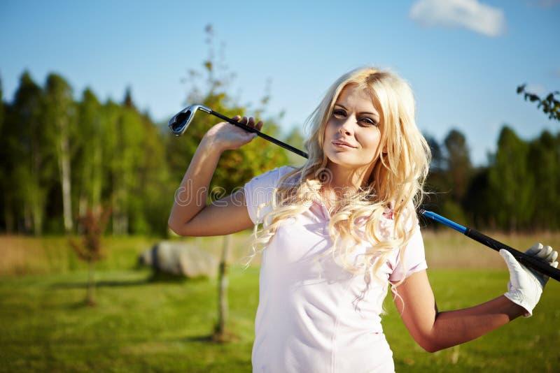 白肤金发的女孩高尔夫球作用 免版税库存照片