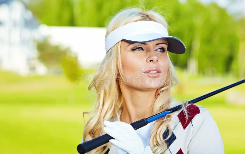 白肤金发的女孩高尔夫球作用 免版税图库摄影