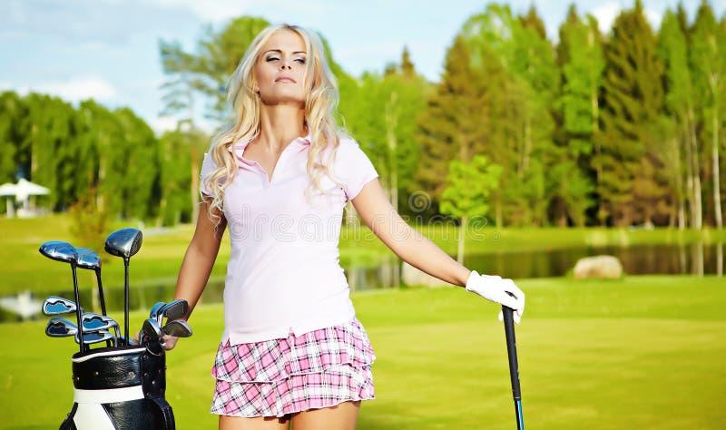 白肤金发的女孩高尔夫球作用 免版税库存图片