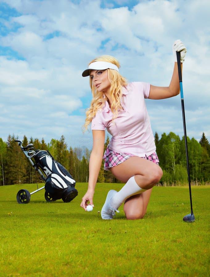 白肤金发的女孩高尔夫球作用 图库摄影