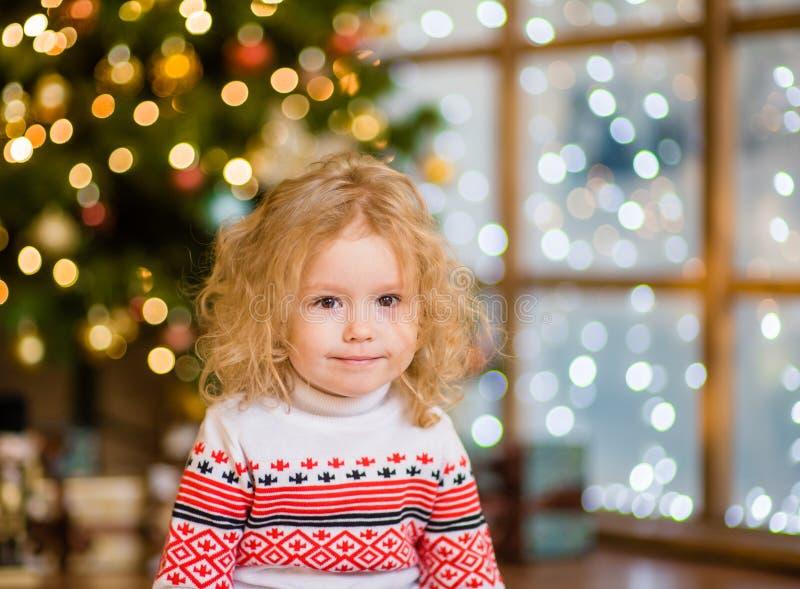 白肤金发的女孩画象圣诞树背景的  库存照片