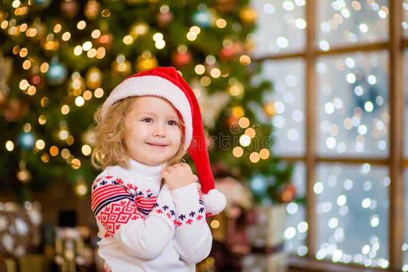 白肤金发的女孩画象红色圣诞老人帽子的在圣诞树背景  图库摄影