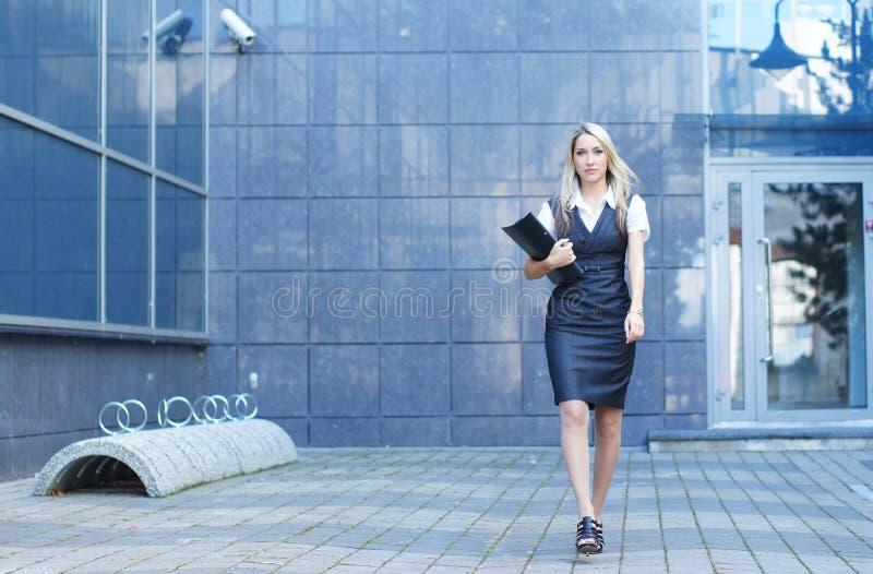 白肤金发的女实业家给正式年轻人穿衣 免版税库存图片