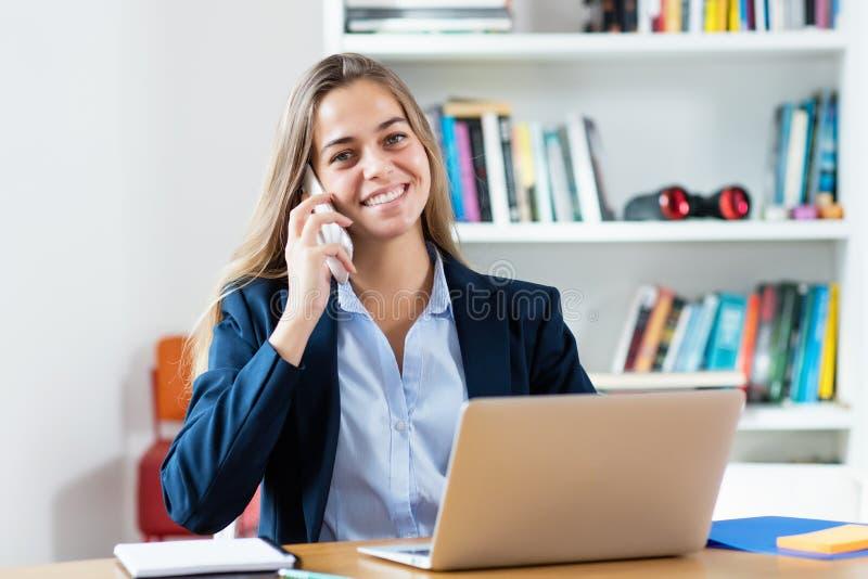 白肤金发的女实业家讲话与顾客在电话 免版税库存照片
