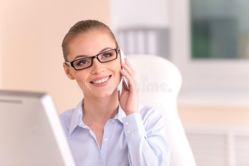 白肤金发的女实业家谈话在电话在办公室 图库摄影