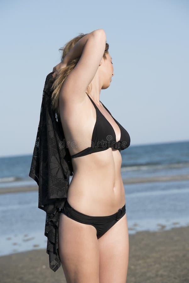 白肤金发的女服黑色比基尼泳装,与布的戏剧 库存图片