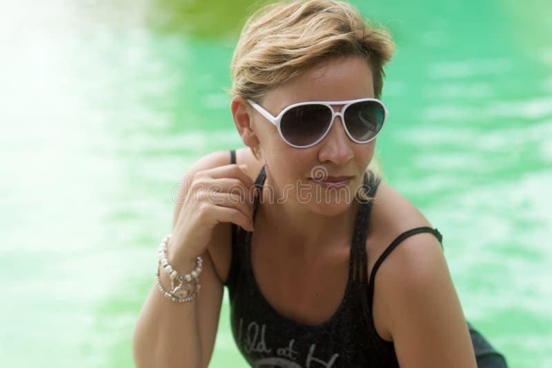 白肤金发的妇女与短的理发的30岁在太阳镜 免版税图库摄影