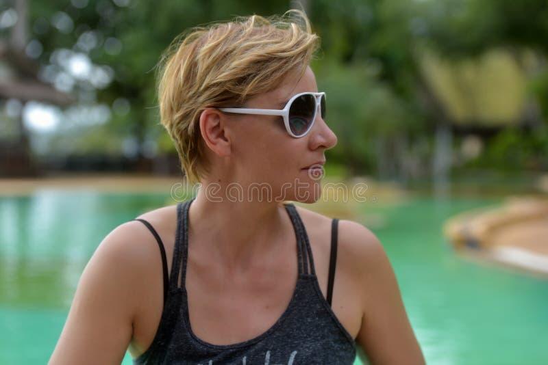 白肤金发的妇女与短的理发的30岁在太阳镜 图库摄影