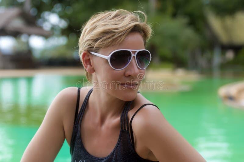 白肤金发的妇女与短的理发的30岁在太阳镜 免版税库存图片