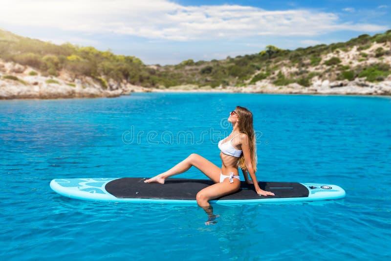 白肤金发的妇女享受在冲浪板的一个热的夏日 库存图片
