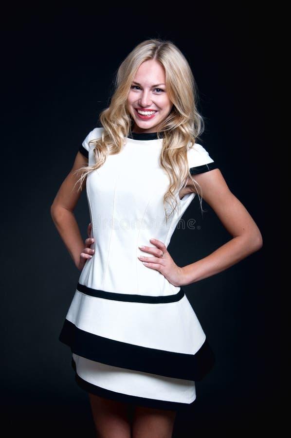 白肤金发的妇女佩带的白色礼服 免版税库存照片