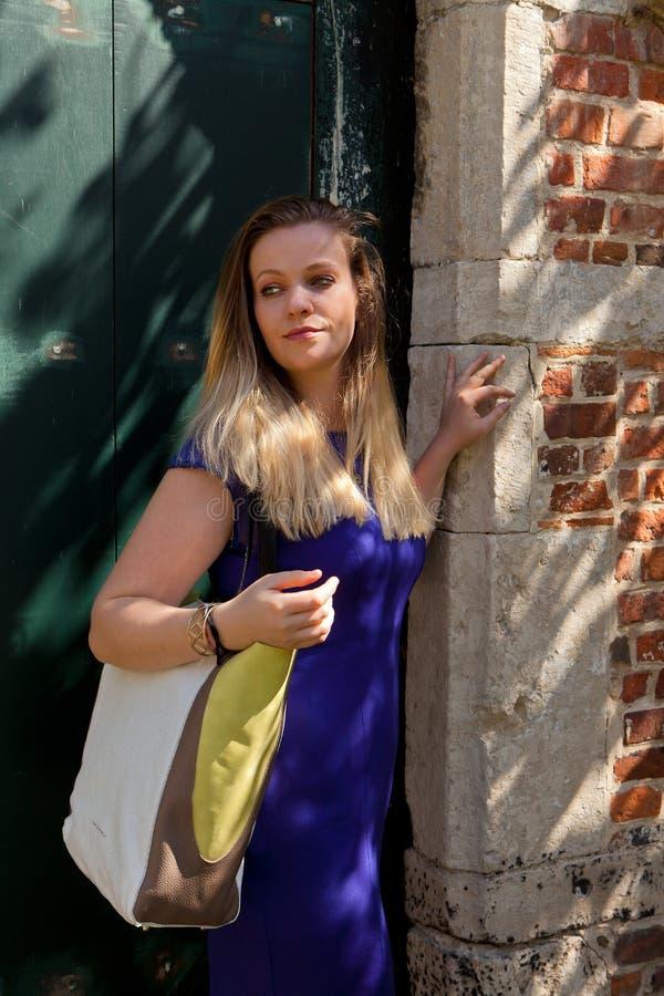 白肤金发的妇女古色古香的门砖墙,格鲁特Begijnhof,鲁汶,比利时 免版税图库摄影
