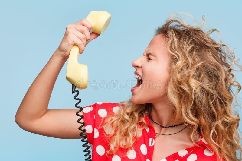 白肤金发的妇女叫喊对电话 库存图片