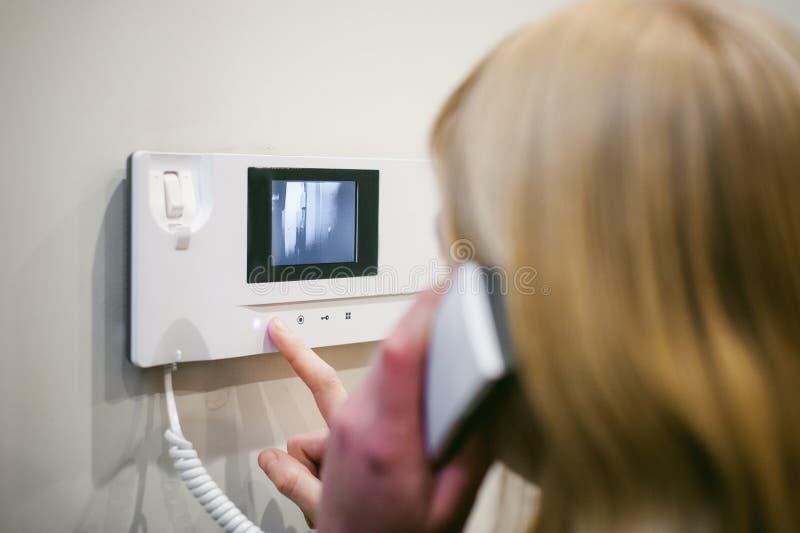 白肤金发的妇女回复对讲机电话 库存图片