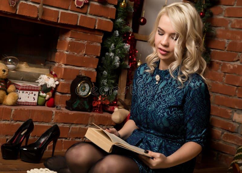 白肤金发的妇女在与圣诞节装饰的壁炉附近读一本书 库存图片
