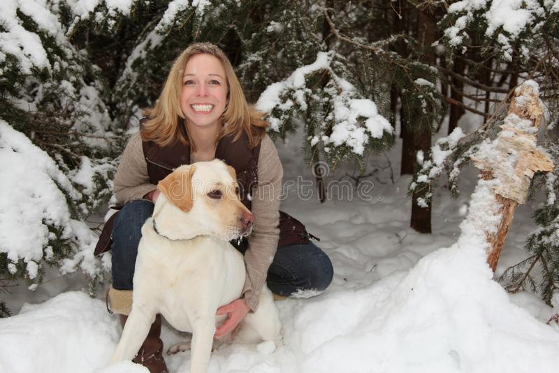 白肤金发的妇女在与狗的冬天 免版税库存照片