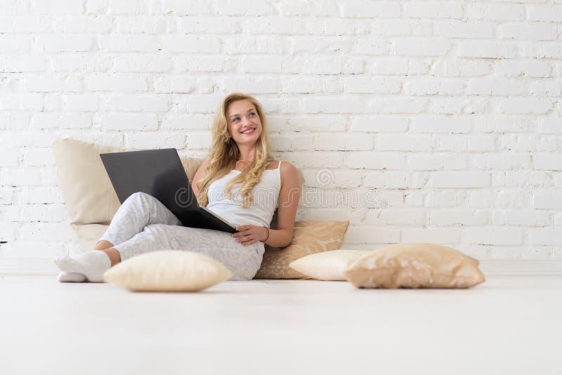 年轻白肤金发的妇女坐地板枕头使用便携式计算机,愉快微笑查寻复制空间的美丽的女孩 库存图片