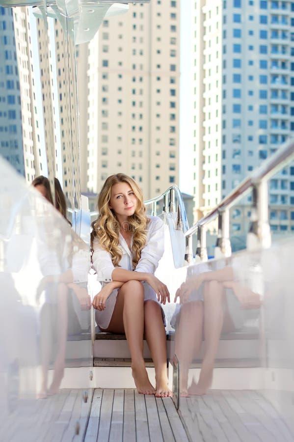 年轻白肤金发的妇女坐游艇 库存图片