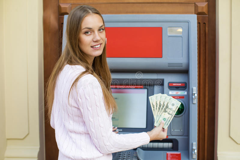 年轻白肤金发的妇女拿着现金美元 库存图片