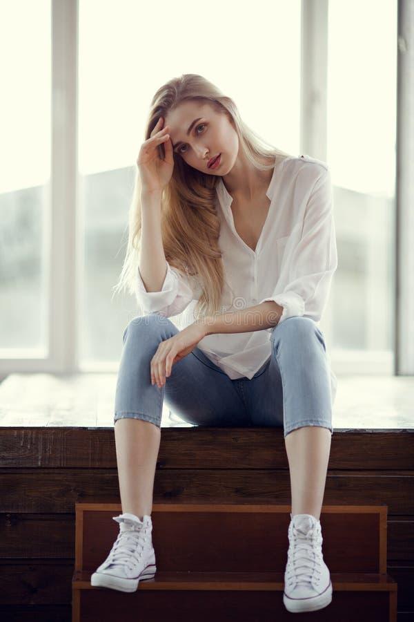 白肤金发的妇女方式纵向 牛仔裤和运动鞋 免版税库存图片