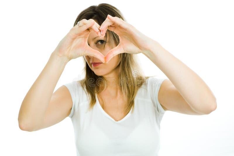 白肤金发的妇女显示心形用手-看通过心脏-爱的标志 免版税库存照片