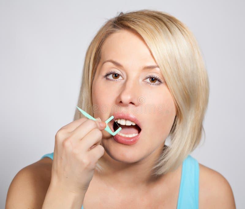 白肤金发的妇女检查她的牙 免版税库存照片