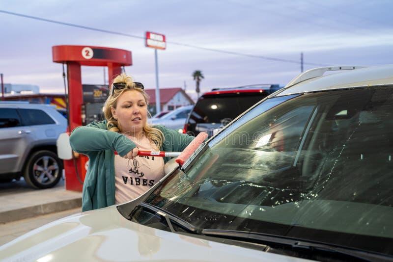 白肤金发的妇女洗涤有橡皮刮板的挡风玻璃,当填装汽车用气体在气体时 库存图片
