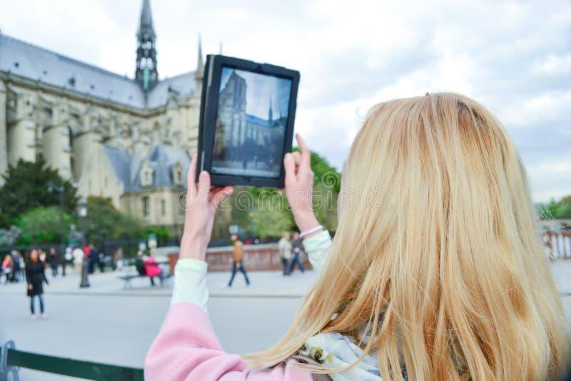 白肤金发的妇女游人在做与Notre Dame的巴黎selfie 库存图片