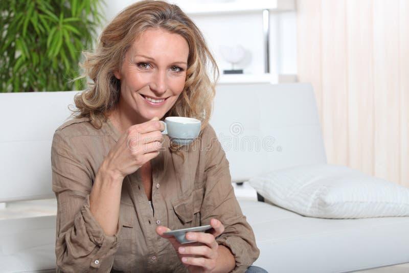 白肤金发的妇女用咖啡 免版税库存图片