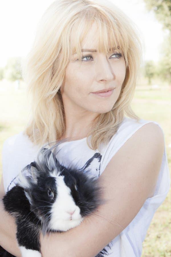 白肤金发的妇女用在她的胳膊的一只兔子 库存图片