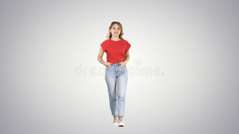 白肤金发的妇女走用在她的口袋的手和谈话与在梯度背景的照相机 库存照片