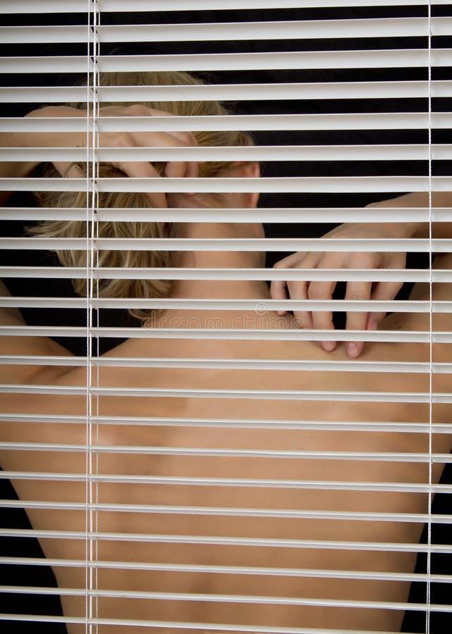 年轻白肤金发的妇女通过窗帘 库存图片