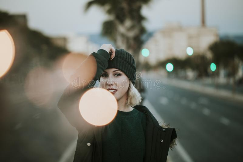 白肤金发的妇女都市画象有编织帽子的在有光的街道中间 库存照片