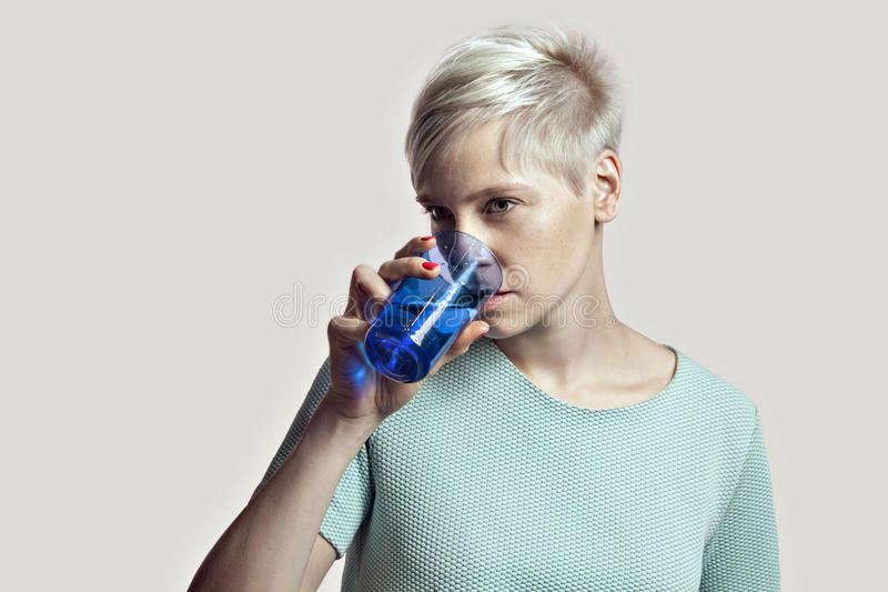 白肤金发的妇女画象有杯的水,短发明亮的背景 免版税库存照片