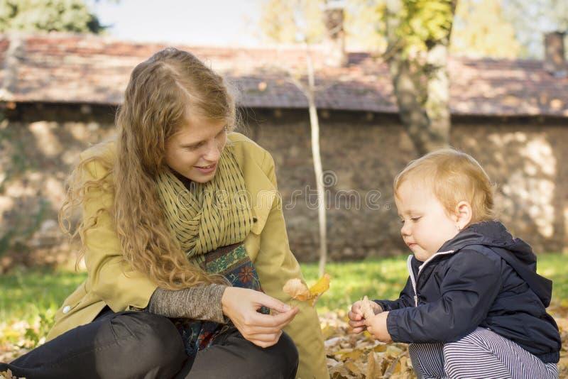 白肤金发的妈妈使用与她的甜女儿在公园 图库摄影