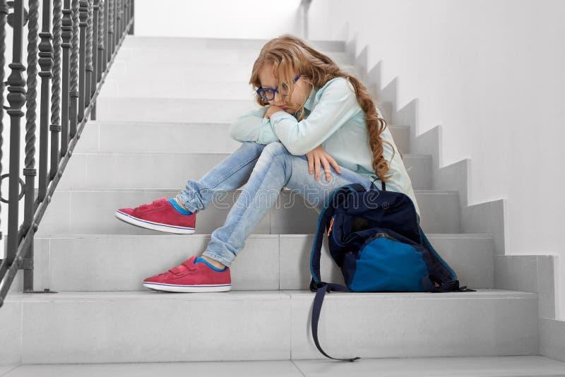 白肤金发的学校女孩坐台阶 库存图片