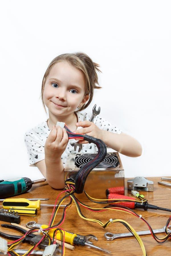 白肤金发的小女孩修理计算机部件 免版税库存照片
