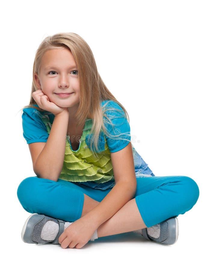 白肤金发的小女孩坐地板 免版税库存照片