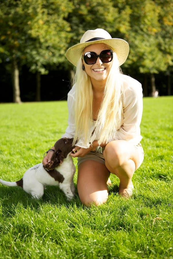 白肤金发的小狗性感的妇女 免版税库存照片
