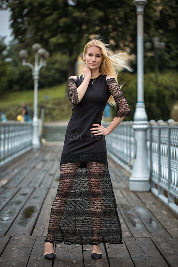 白肤金发的少妇室外生活方式画象停留在街道上的桥梁的时髦的黑礼服的 秋天,雨天 库存照片