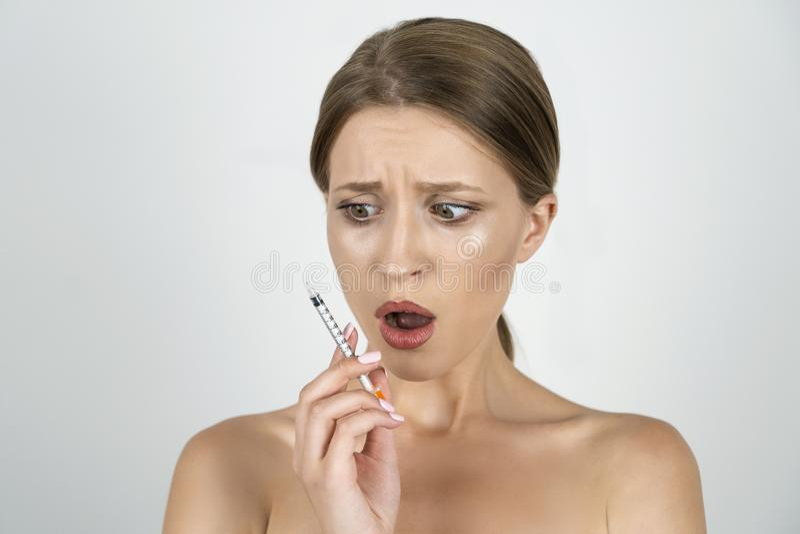 白肤金发的年轻女人藏品注射器在她的看起来害怕的接近被隔绝的白色背景的手上 免版税图库摄影