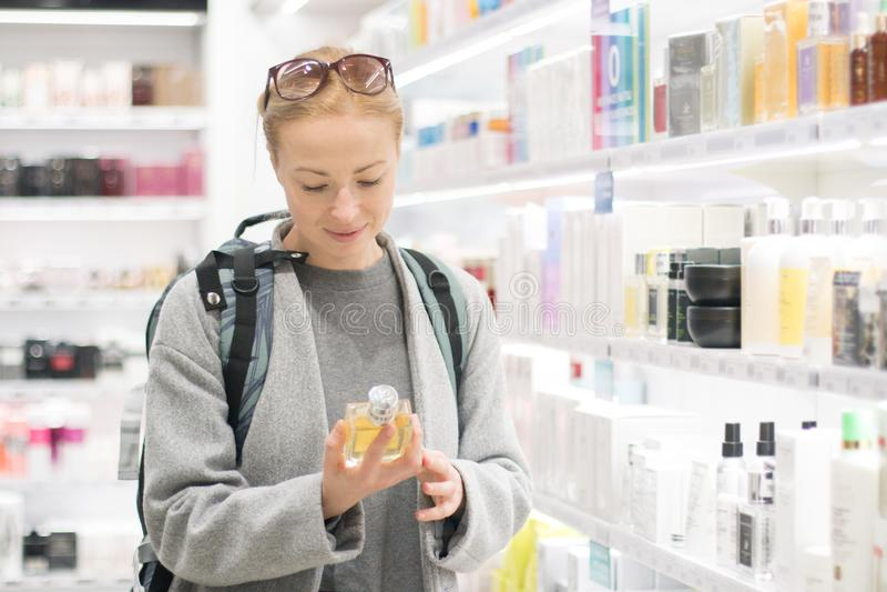 白肤金发的年轻女性选择香水的旅客佩带的旅行背包在机场免税商店 免版税库存图片