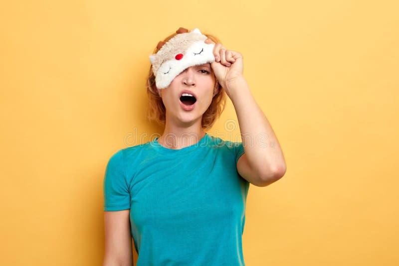 白肤金发的年轻疲乏的妇女佩带的睡觉面具 免版税库存照片