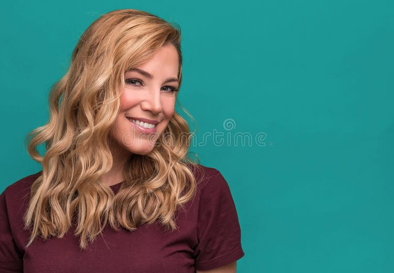 白肤金发的微笑的妇女画象蓝色背景的 库存照片