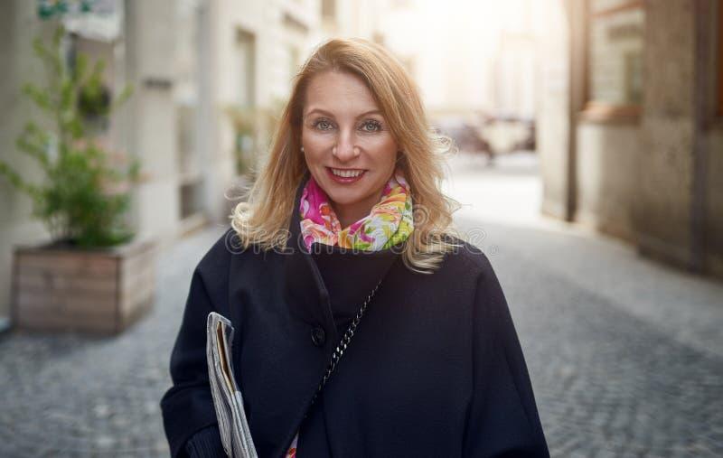 白肤金发的成熟微笑的妇女室外画象  免版税图库摄影