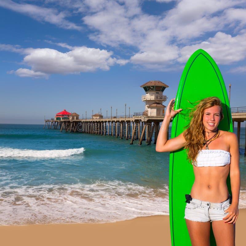 白肤金发的拿着在海滩的冲浪者青少年的女孩冲浪板 免版税库存照片