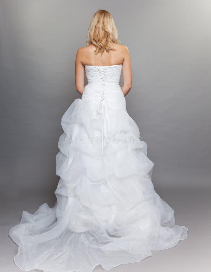 白肤金发的新娘白色长的婚礼礼服在灰色观看 免版税图库摄影