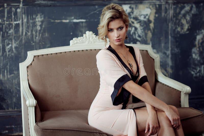 白肤金发的方式头发设计 年轻可爱的妇女,选址在沙发,葡萄酒样式 免版税图库摄影