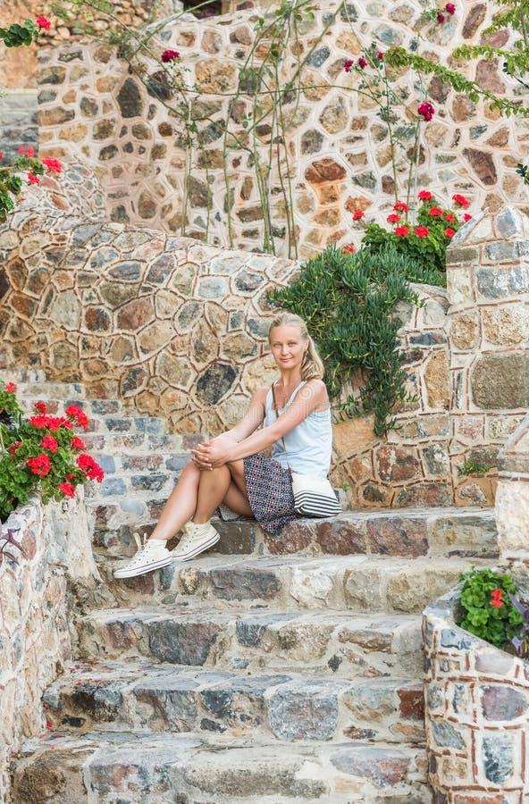 年轻白肤金发的旅游妇女坐古老石台阶在老城市,阿拉尼亚,土耳其 免版税库存图片