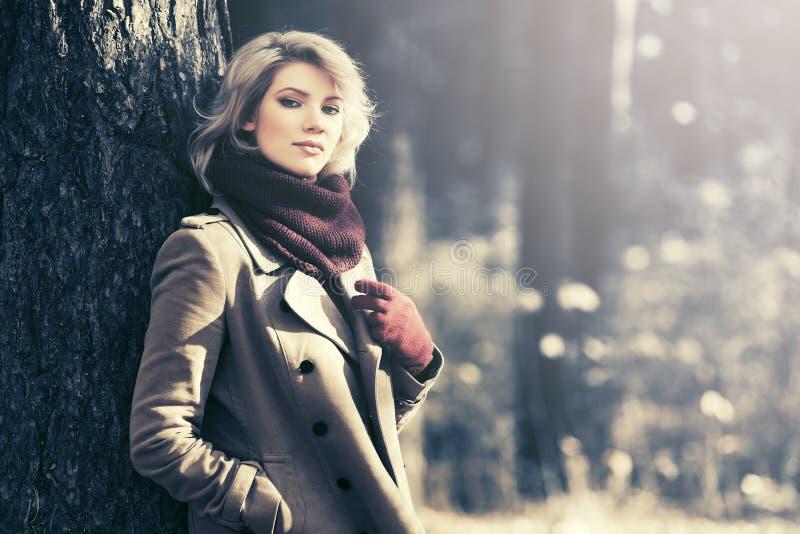 年轻白肤金发的时尚妇女在秋天森林里 免版税图库摄影